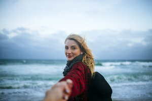 Young woman taking hand of a man on the beach - KIJF01201