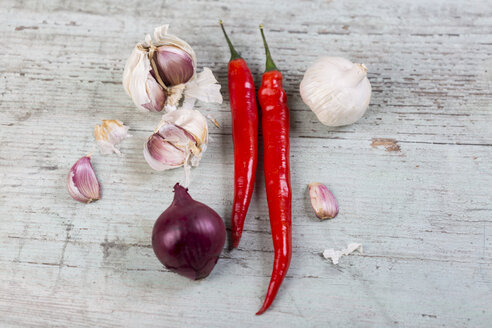 Red chili pods, red onion and garlic on wood - JUNF00828