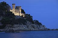 Spain, Catalonia, Lloret de Mar, Costa Brava coast at night, castle on cliff top - ABOF00158
