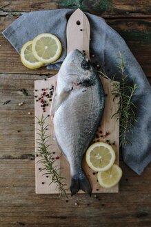 Sea Bream on a wooden board with pepper and rosemary - GIOF01850