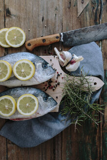 Sea Breams on a wooden board with spices and herbs - GIOF01853