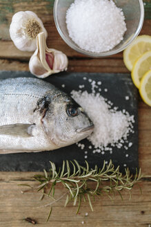 Sea Bream on a slate board with rosemary, lemon and salt and garlic - GIOF01856