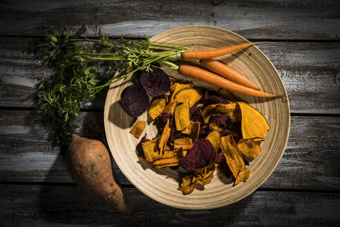 Vegetable chips made of carrots, sweet patatoes and beetroot on plate and dark wood - MAEF12136