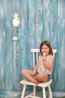 Little girl sitting on chair eating lemon ice lolly - RTBF00650