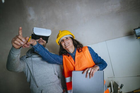 Woman on construction site showing a man with virtual reality glasses the house - KIJF01217