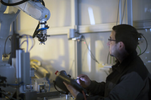 Man looking at robot arm in a sensor technology plant - SGF02107