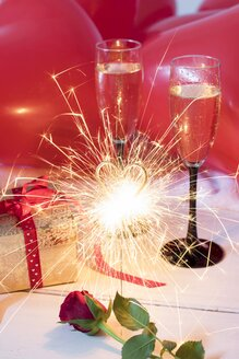Red rose, sparkler, gift, champagne glasses and balloons - YFF00638