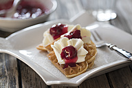Plate of waffles with whipped cream, cherries and cherry groats - YFF00641