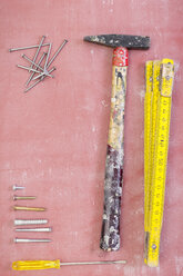 Used tools, nails and screws on pink ground - CMF00639