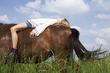 Girl lying on horseback - FSF00775