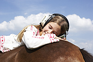 Girl with headphones  lying on horseback - FSF00781