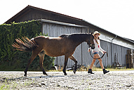 Girl walking with horse on farm - FSF00784