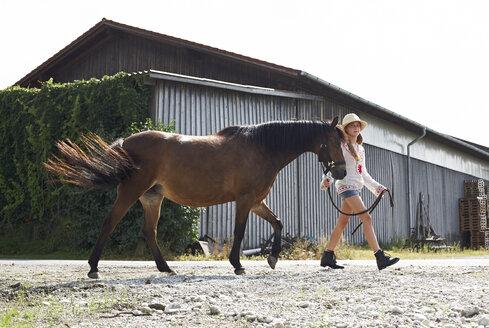 Girl walking with horse on farm - FSF00784