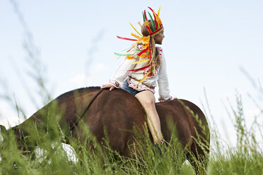 Girl wearing feather headdress riding horse on meadow - FSF00787