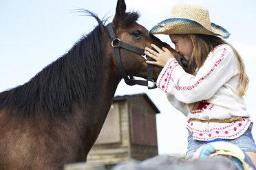 Girl wearing straw hat kissing horse - FSF00790