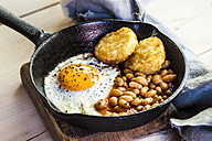 Fried egg, baked beans and hash browns in frying pan on wooden board - SBDF03150
