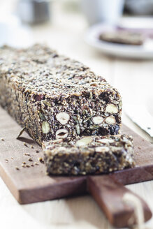 Home-baked wholemeal gluten-ree bread with nuts and seeds on wooden board - SBDF03153
