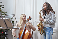 Two girls playing cello and saxophone at Christmas tree - RHF01805