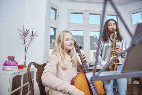 Two girls playing cello and saxophone together - RHF01811