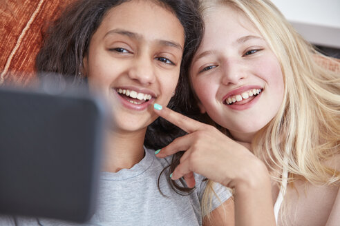 Two laughing girls looking at smartphone - RHF01817
