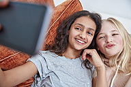 Two happy girls on couch taking a selfie - RHF01820