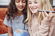 Two happy girls using smartphone - RHF01835