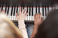 Close-up of two girls playing piano together - RHF01841