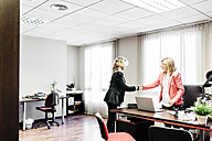 Two businesswomen shaking hands in office - JRFF01187