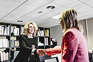 Two businesswomen shaking hands in office - JRFF01190
