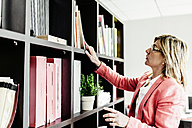 Businesswoman looking at documents in bookshelf - JRFF01202