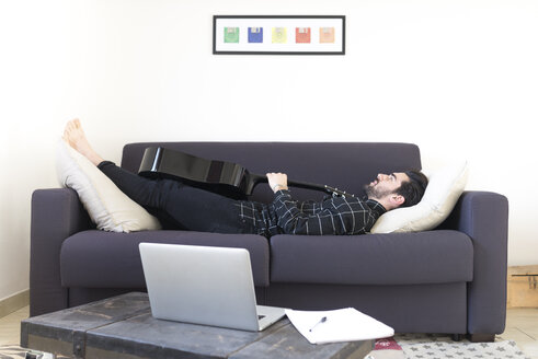 Young man at home lying on couch with guitar - FMOF00149