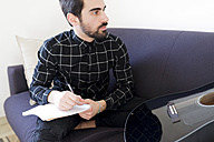 Young man at home sitting on couch with notepad and guitar - FMOF00152