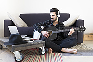 Young man at home playing guitar and wearing headphones connected to laptop - FMOF00155