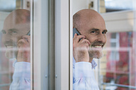 Smiling businessman on cell phone at the window - FKF02128