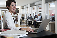Portrait of happy woman using laptop in office with colleagues in background - FKF02134