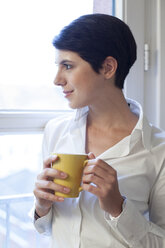 Woman holding cup of coffee looking out of window - FKF02152
