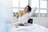Smiling woman holding cup of coffee at desk in office - FKF02155
