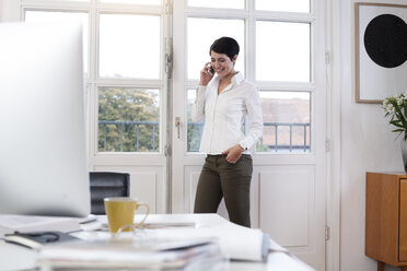 Woman standing at the window in office talking on phone - FKF02158