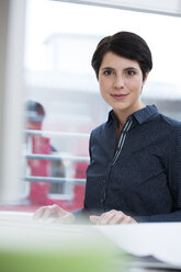Portrait of smiling woman at desk in office - FKF02164