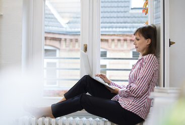 Woman using laptop at the window - FKF02173