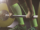 Close-up of woman preparing to lift barbell - MADF01330