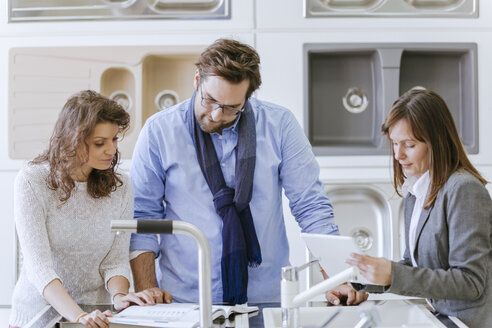 Customers consulting saleswoman in shop for kitchen sinks - ZEDF00508