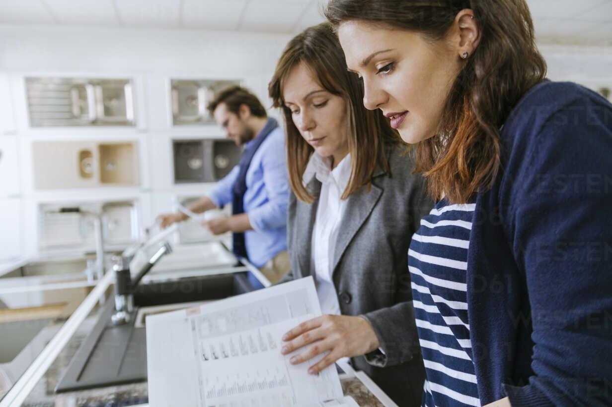 Customers consulting saleswoman in shop for kitchen sinks - ZEDF00517 - Zeljko Dangubic/Westend61