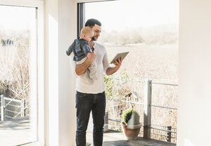 Father standing at home, carrying baby son and reading text messages - UUF09871