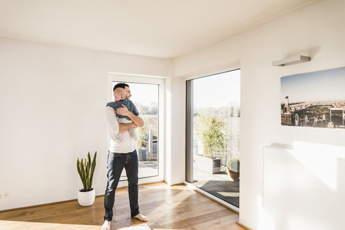 Father holding and hugging his baby son, standing in comfortable home - UUF09874
