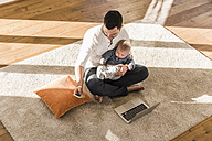 Father sitting cross-legged with baby son on lap, using laptop and smart phone - UUF09883