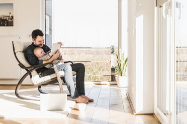 Father sitting in arm chair with baby son on lap, using mobile devices - UUF09892