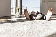 Father and baby son sleeping on carpet, view of bare feet - UUF09895