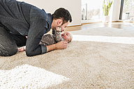 Father and baby son playing on carpet at home - UUF09898