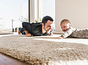 Father and baby son playing crawling on carpet - UUF09901